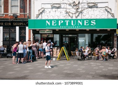 Southend, UK - 21 April 2018: Day-trippers queue outside Neptunes restaurant on Southend seafront for fish and chips on a warm day in April