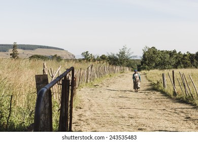 Southern Africa - March 27, 2012: A woman walks down a dirt path alone