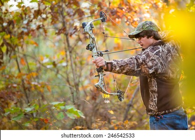 southern american teen boy out in the woods bow hunting for deer