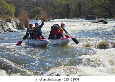 SOUTHERN BUG RIVER, UKRAINE - MARCH 30, 2014: Sport catamaran is fused on the rapid river with two persons