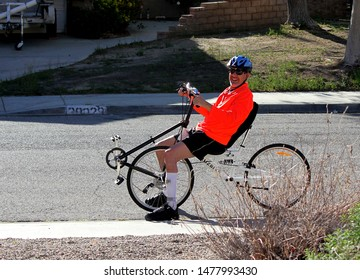 Southern CA, USA, March 23, 2016: A man with a handicapped leg rides a recumbent bike for exercise and transportation.
