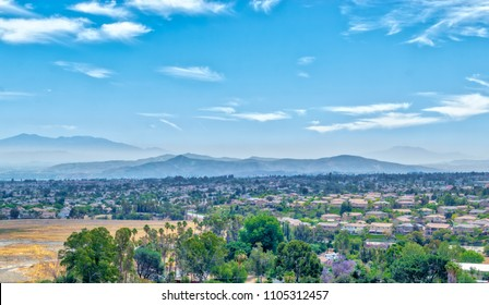 Southern California suburbs in early summer with smog covering area near distant foothills