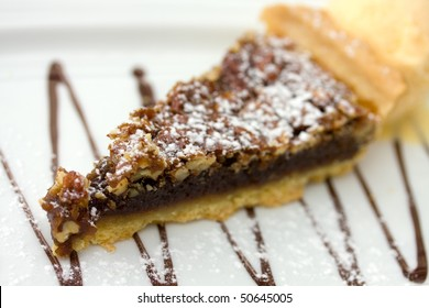 Southern chocolate chip walnut-pecan  pie isolated over white. Shallow DOF.