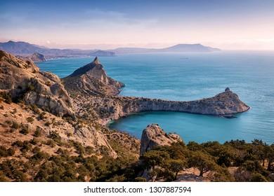 The southern coast of the Crimea at dawn. New world (Novy Svet). Winter seascape. Crimea. Eastern Europe. Soft light. Pink Bright Sky