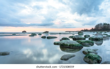 Southern coast of the Finnish Gulf. Rocks covered with green seaweed in the Baltic sea. Smooth transparent reflective water. Orange sunset markings under the low altitude clouds. Estonia, Baltic