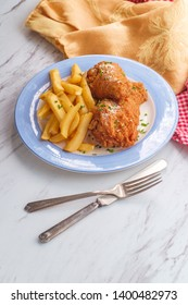 Southern cuisine seasoned and battered fried chicken drumsticks with side of steak fries