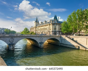 Southern facade of the Palace of Justice with towers, river Seine, her embankment and bridge in the foreground in Paris