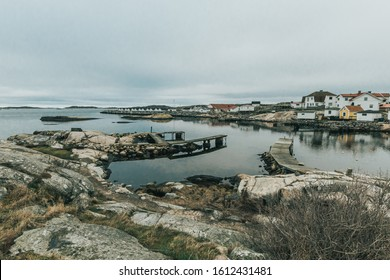 Vrångö, Southern Gothenburg Archipelago / Sweden - 24 December 2019: A view of sea shore, a rocky landscape of Vrångö island and its scandinavian wooden houses in Sweden during a cloudy day.