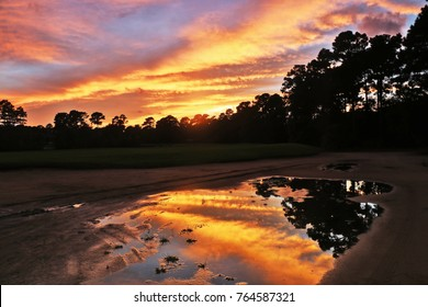 Southern landscape with golf course at dusk and bright colors sky reflects in puddle during after rainy day sunset. Pawleys Island, Myrtle Beach area, South Carolina, USA.Spectacular nature background