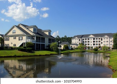 Southern modern architecture and vacation rentals background. Myrtle Beach suburb neighborhood morning view with buildings around the pond with sprinkling fountain. South Carolina, USA.