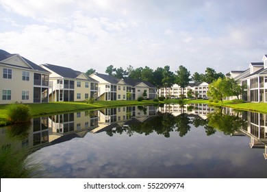 Southern residential neighborhood< South Carolina<USA. Modern neighborhood with buildings around the pond.Houses and trees reflected in the tranquil water during cloudy morning.Horizontal composition.