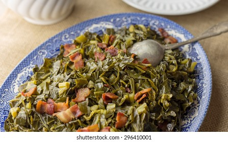 Southern style collard greens with bacon served on an antique plate with burlap table runner.