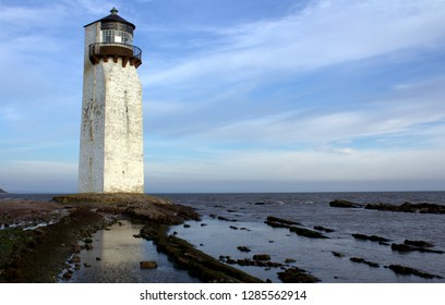 Southerness Lighthouse, rocky beach in the foreground in Dumfries and Galloway, Scotland.