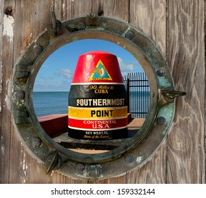 The  Southernmost Point In The Continental USA Buoy in Key West, Florida, as seen through a rustic old porthole.