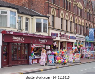 southport, merseyside, united kingdom - 28 june 2019: a row of shops neville street in southport merseyside selling ice cream rock beach toys snacks and candyfloss with and amusement arcade