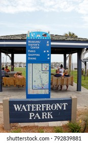 Southport, NC, USA - July 28, 2014: Waterfront Park sign below a Southport attractions map and guide. People near Southport guide map with Waterfront Park sign