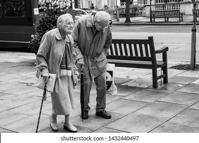 Southport, UK. October 2017. An old couple walking slowly along the street. They are in step; both walk with the aid of a stick and an umbrella. The man is stooped with age. The lady looks forward.
