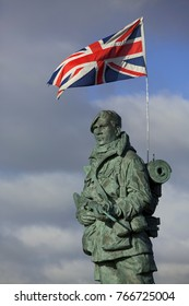 SOUTHSEA ENGLAND; DECEMBER 1ST 2017. Royal Marine statue outside the RM Museum in Portsmouth Hampshire.  Strong wind setting the flag flying proud which is attached to the Marine's back pack.