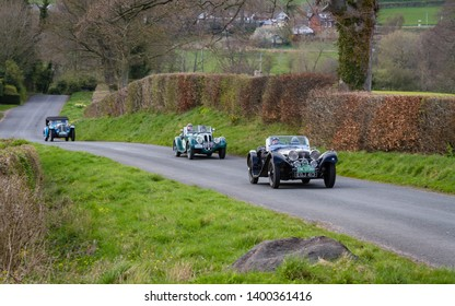 SOUTHWAITE, ENGLAND - APRIL 5: A procession of vintage cars climb Southwaite Hill in Cumbria, England on April 5, 2019. The cars are taking part in the 11th Flying Scotsman Rally, a free public-event.