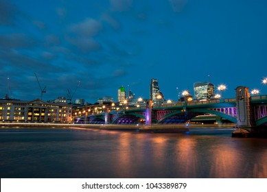 Southwark Bridge from the south bank of the River Thames in the early evening.