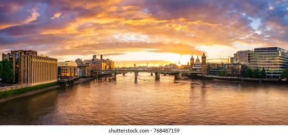 Southwark bridge waterfront panorama at sunset. London, England