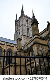 Southwark Cathedral. Tower with golden clock and black iron fence. South Bank, London, United Kingdom.