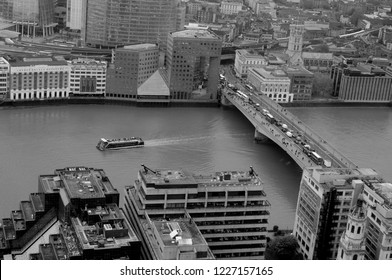 Southwark, London / UK - 11/09/2018: River cruiser passing under London Bridge from the Skygarden of the Walkie Talkie building.