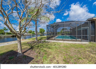 Southwest Florida homes on a canal.  View of canal homes near the screened cage surrounding the pool in one of the homes.