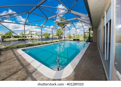 Southwest Florida homes on a canal.  View of canal homes through the screened cage surrounding the large swimming pool in one of the homes.