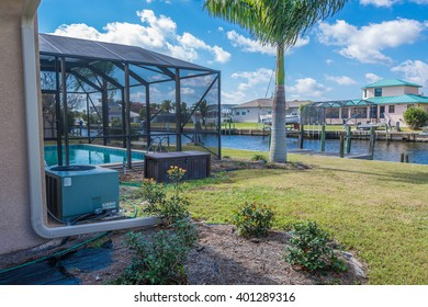 Southwest Florida homes on a canal.  View of canal homes and screened cage surrounding the pool in one of the homes along with the a/c unit sitting in the landscaping beds.