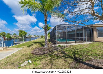 Southwest Florida homes on a canal.  View of canal home and screened cage surrounding the pool in one of the homes, boat docks and boat lift.