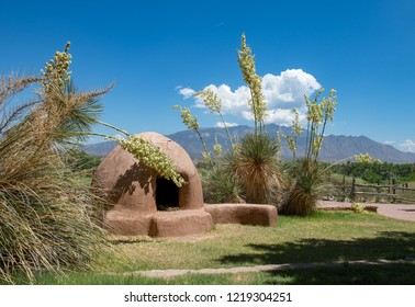 Southwestern Horno Clay Oven with Tall Yucca Blooms, Blue Sky, Clouds  and Mountains.