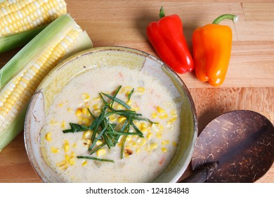 Southwestern style corn chowder soup garnished with ears of corn along with red and yellow bell peppers