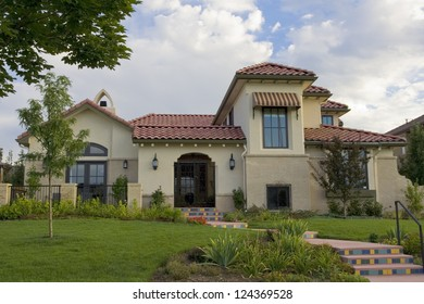 A southwestern style stucco house with red roof, in an upscale family neighborhood.