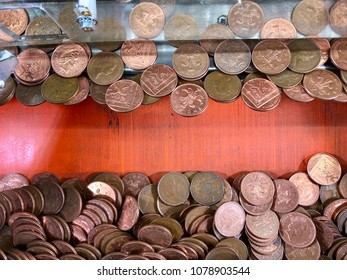 SOUTHWOLD, SUFFOLK - APRIL 24, 2018: British two pence pieces piled on a moving coin pusher machine at an amusement arcade in Southwold, Suffolk, UK.