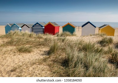 Southwold, Suffolk. England. UK. March 2019. Looking out to sea over some colourful beach huts on the sandy beach at Southwold. Suffolk.