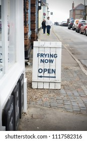Southwold, UK - March 25 2018:  A street sign for frying time at a fish and chip shop in a seaside town in Suffolk