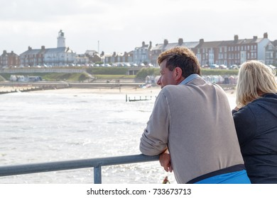 Southwold, UK - September 10, 2017 - Two tourists looking over the beautiful view of Southwold from the pier