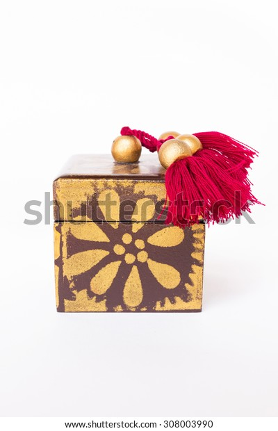 Souvenir box decorated with gold paint and red tuft isolated on white background