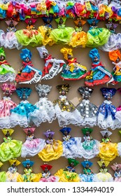 Souvenir figurine magnets featuring good luck Brazilian wish ribbons decorating the traditional costume dresses of miniature figurines on display in Salvador, Bahia, Brazil