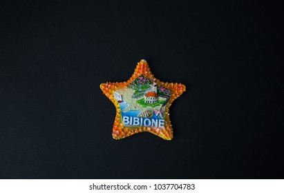Souvenir - Fridge magnet from Bibione, Italy on black background
