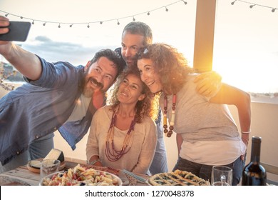 Souvenir photo with friends, evening on the beach, terrace with sunset behind, selfie with cell phone, happy and carefree friends, summer evening parties, beach holidays, smiles and photographs