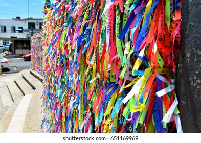 """Souvenir tapes with the words """"Souvenir of Our Lord of Bonfim"""", tied in the grids of the church of Our Lord of Bonfim in Salvador, Bahia, Brazil."""