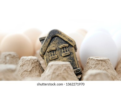 Souvenir toy building, Golden house in a tray with eggs on a light background. White and brown eggs. Concept happy birthday to a new home. Mortgage or home loan.
