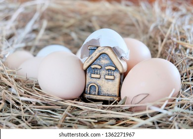 Souvenir toy in the hay. Broken shell on the Golden house. Birth house concept. New housing. Mortgage, purchase of housing.