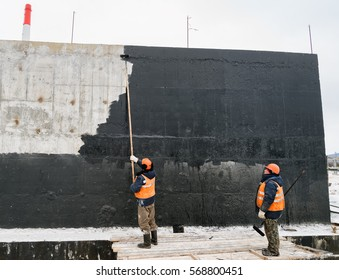 SOVETSKAYA GAVAN, RUSSIA - JANUARY 16, 2017: Two workers paint a wall of a building waterproofing paint