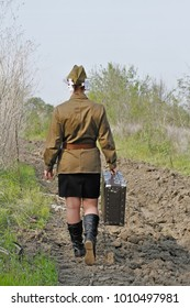 Soviet female soldier in uniform of World War II with suitcase goes on a plowed road (rear view)