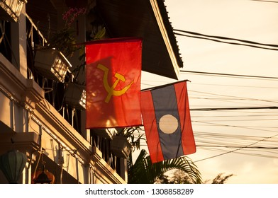 Soviet and Lao flags hanging together on the french colonial building on Sisavangvong road in old quarter in Luang Prabang, Laos
