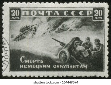 SOVIET UNION - CIRCA 1942: A stamp printed by the Soviet Union Post is entitled Death to German Invaders!, circa 1942. It shows Russian artillerymen shooting at fascist tanks.