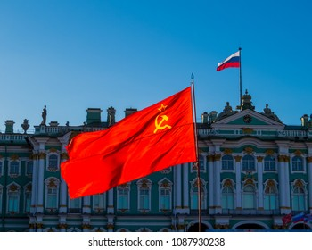 Soviet Union flag with the Russian flag and the Hermitage Museum in the background. In St. Petersburg, Russia